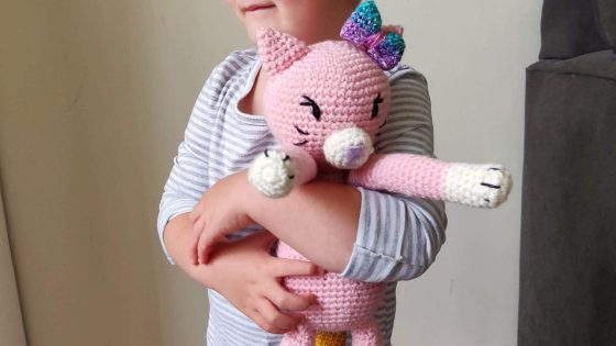 Little girl holding a pink crochet cat called Lucy.