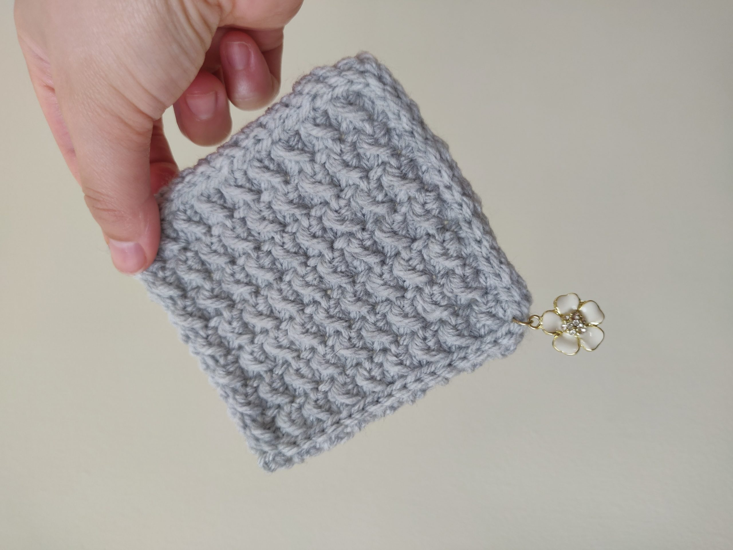Crochet coaster with slip stitch edging and charm in the corner.