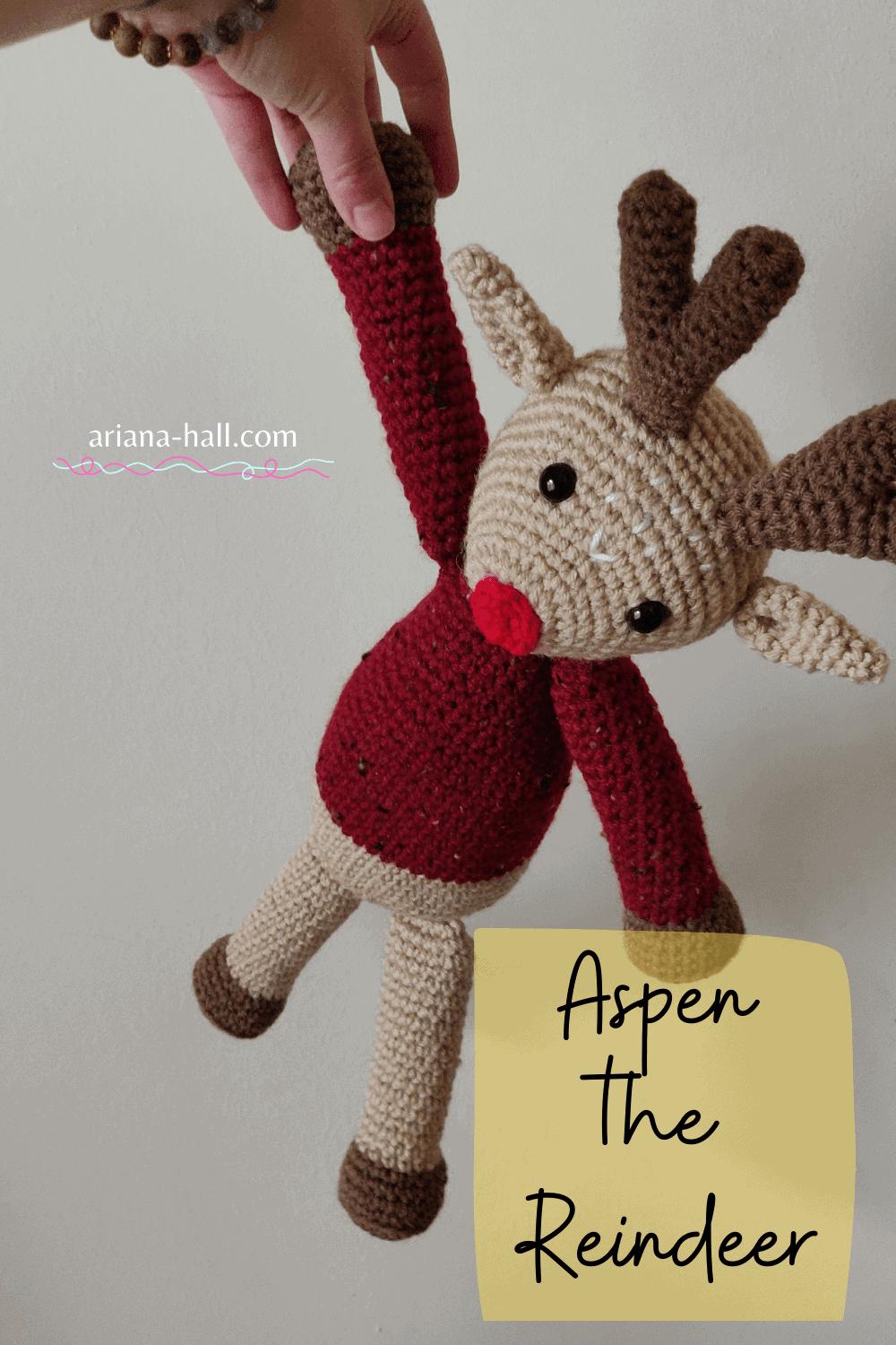 Crochet reindeer held by one limb.