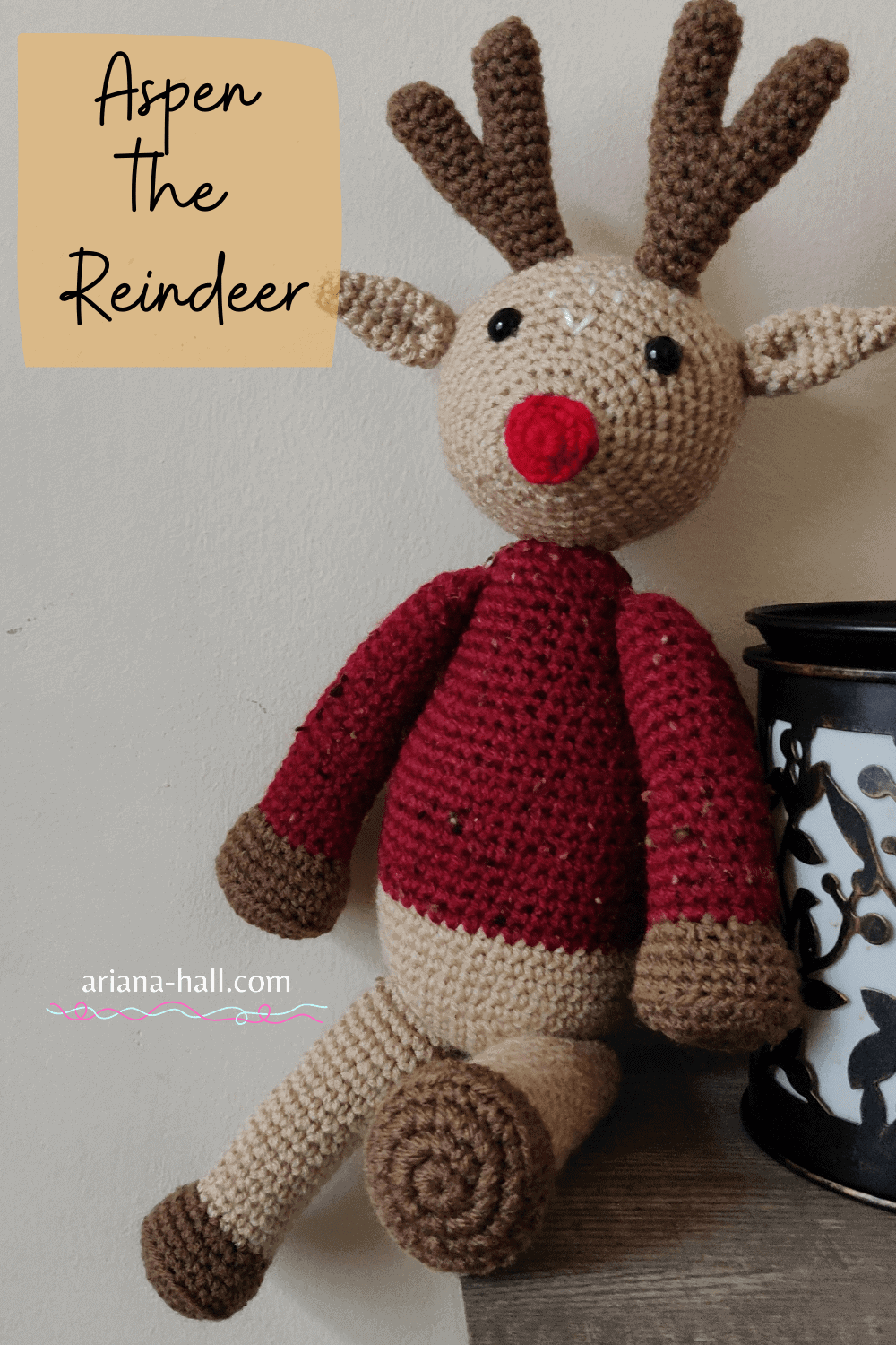 Crochet reindeer with a bright red nose sitting on a table.