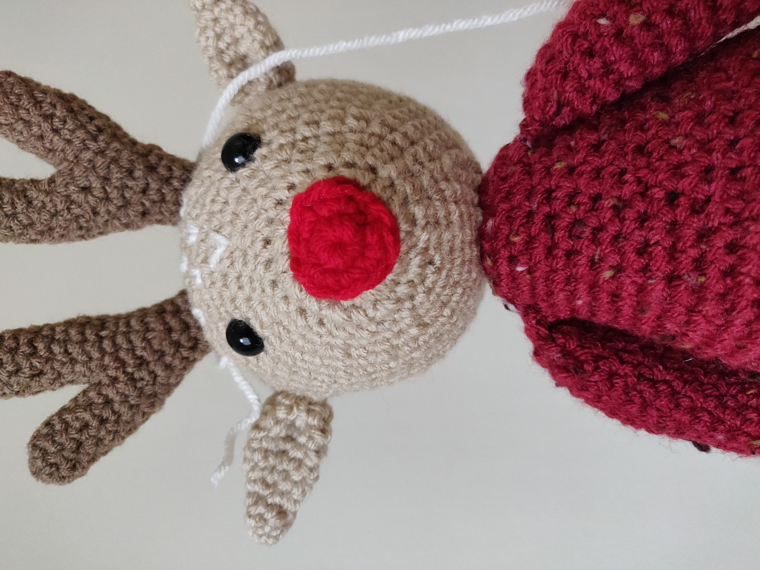 Crochet reindeer with dark red sweater and cherry red nose.