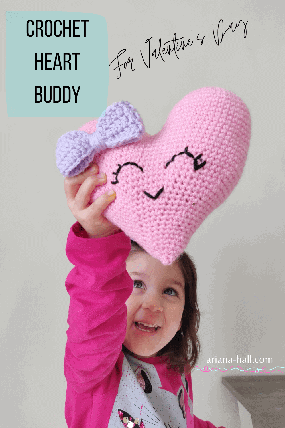 Child holding up a crochet heart with a purple bow and smile.