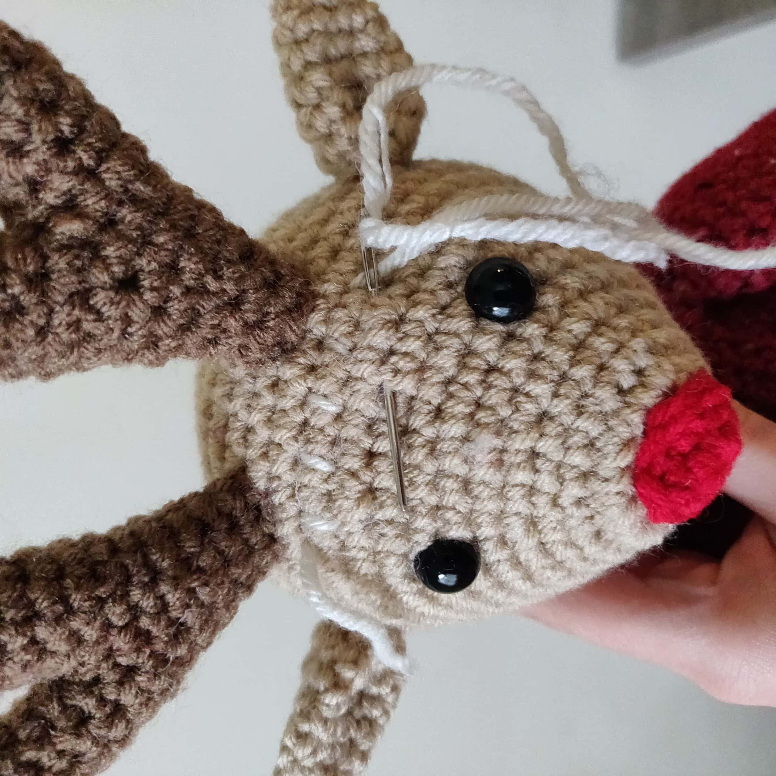 Sewing Aspen the reindeer with white yarn.