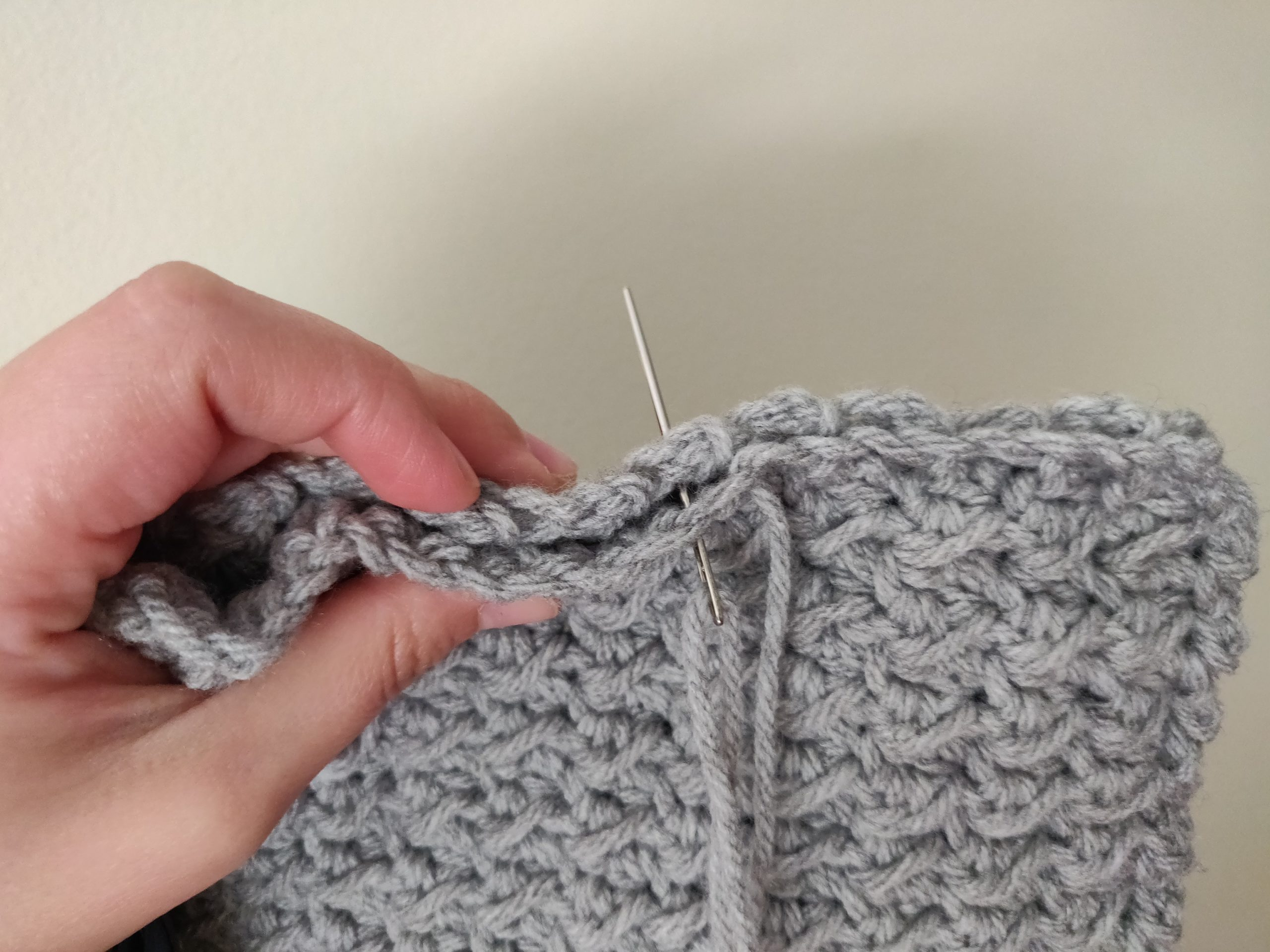 Sewing the edges of the scarf closed.
