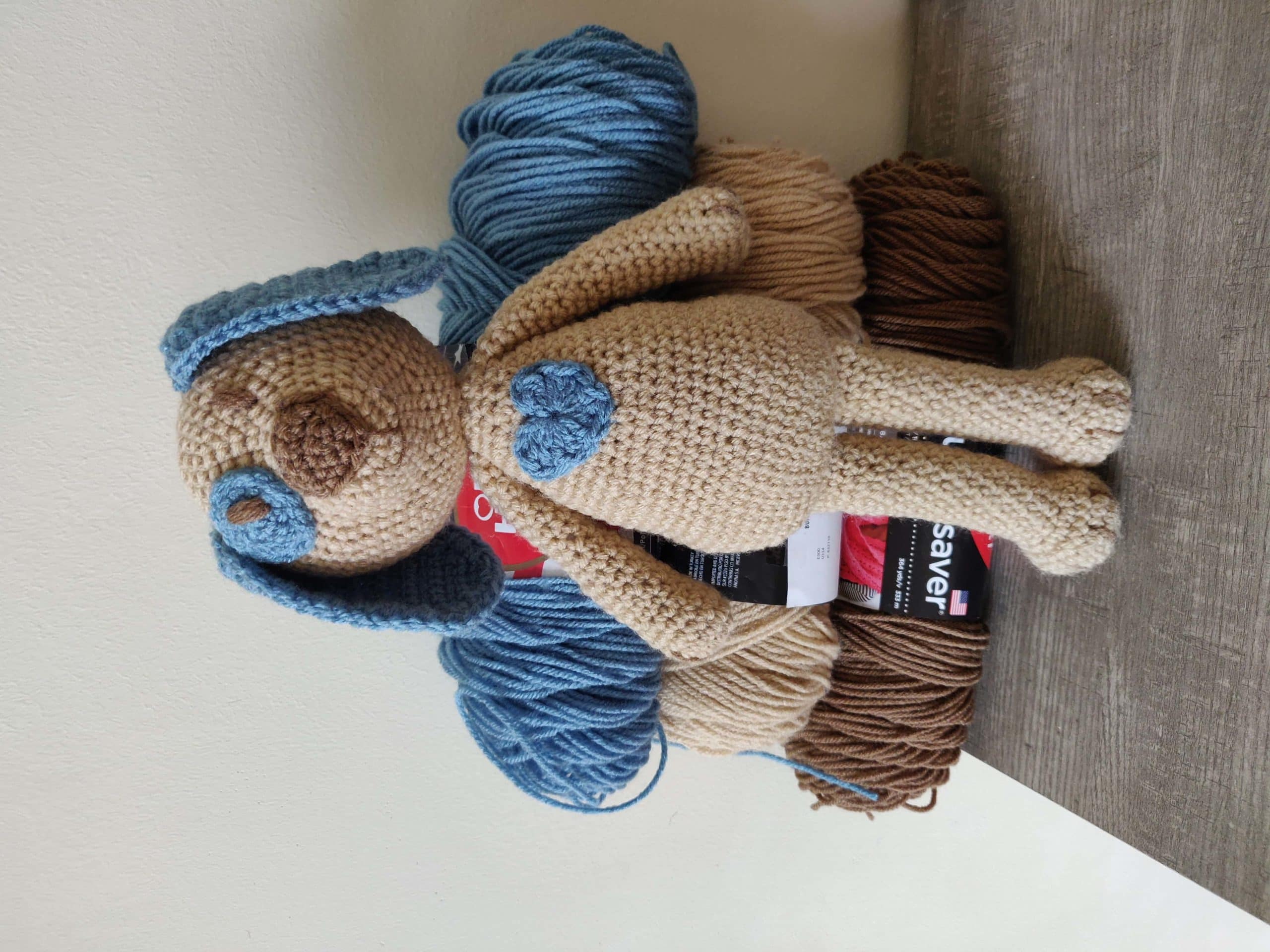 Crochet dog with brown and blue. Yarn in the back.