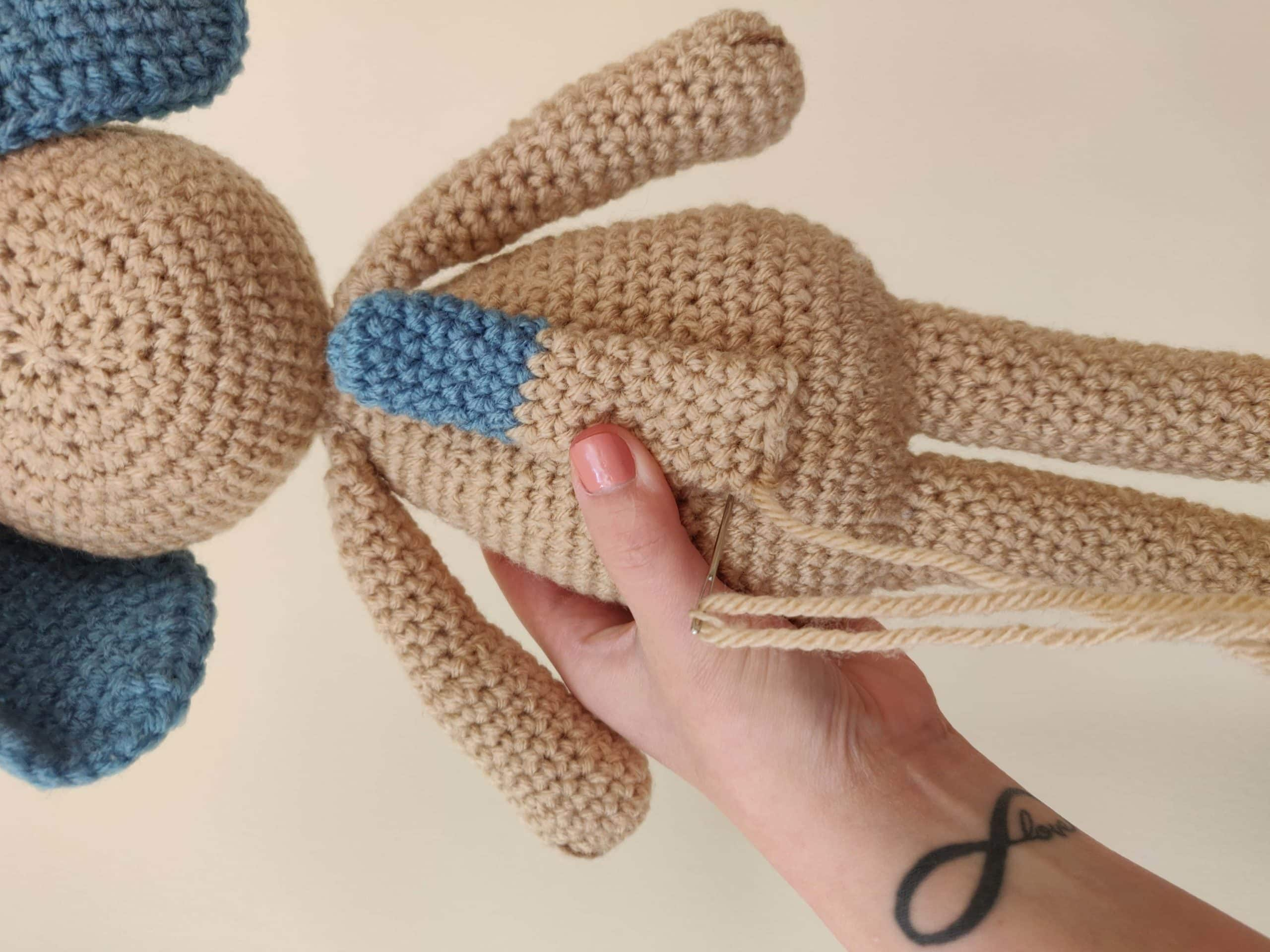 Sewing the tail on the crochet dog.