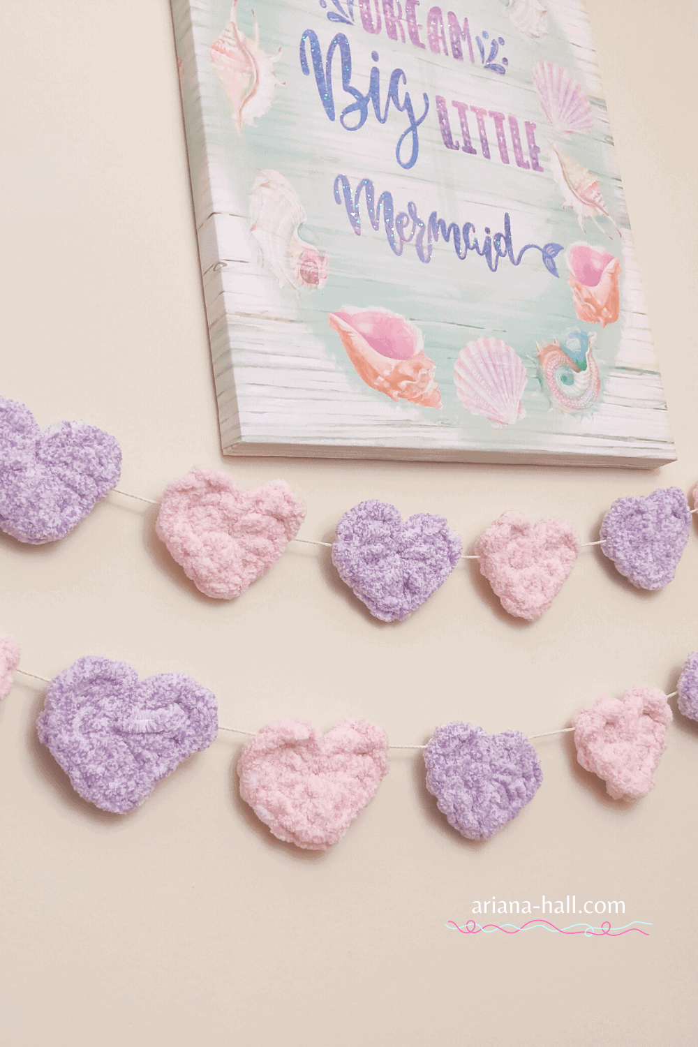 Pink and purple yarn heart garland hung on the wall.