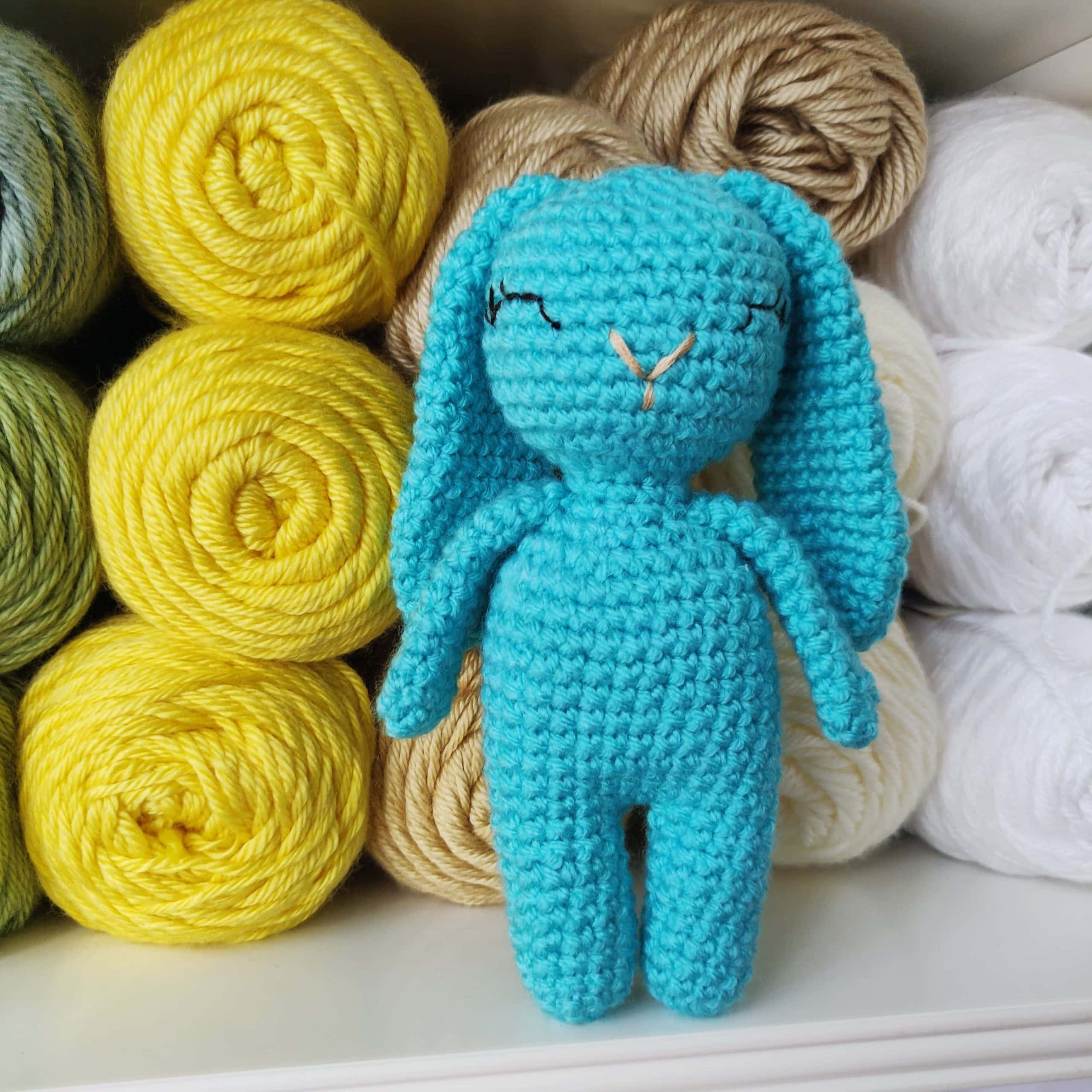 Small blue crochet bunny with closed eyes.