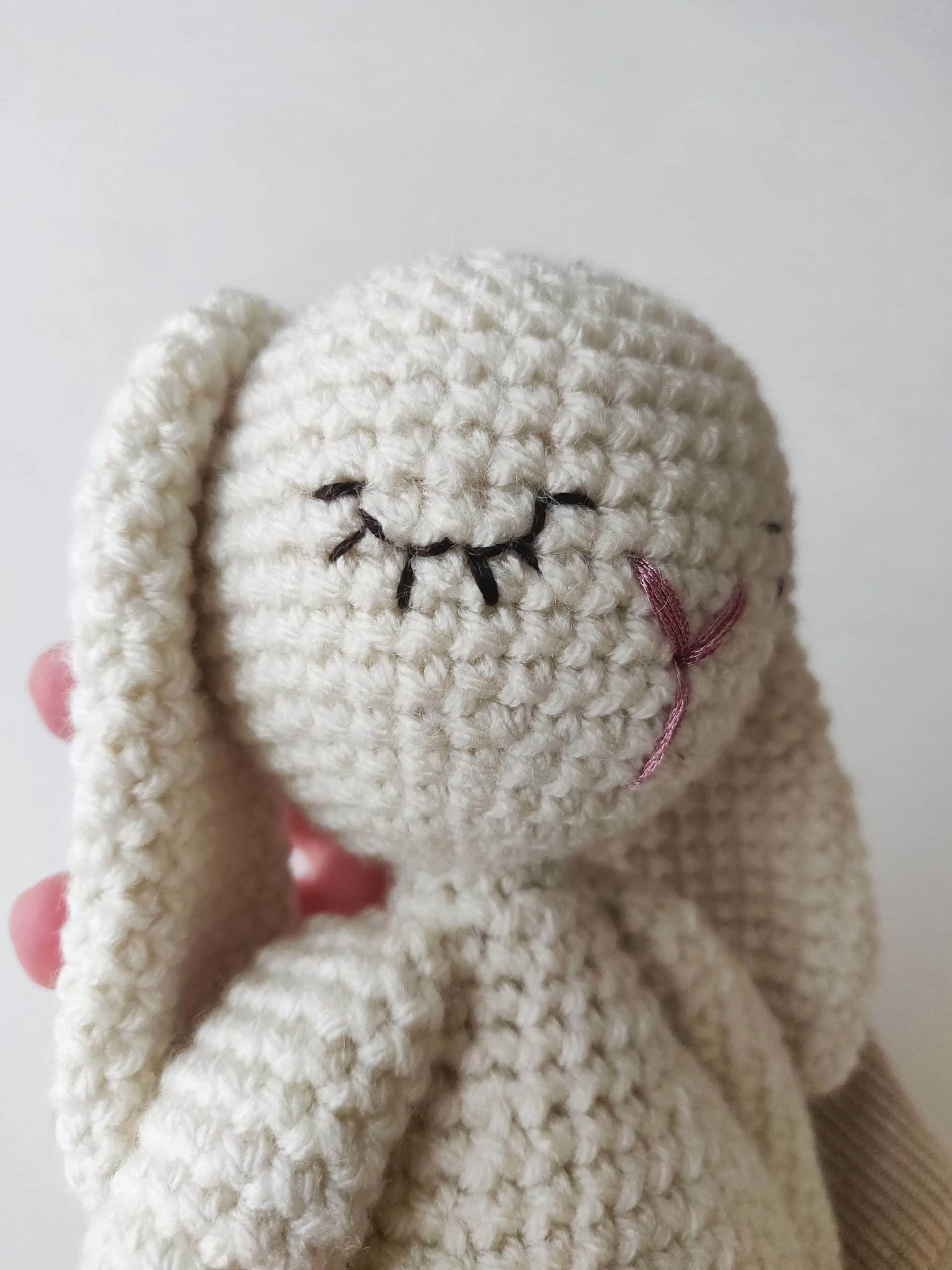 White crochet bunny facing to the side with embroidered eyes and eyelashes.