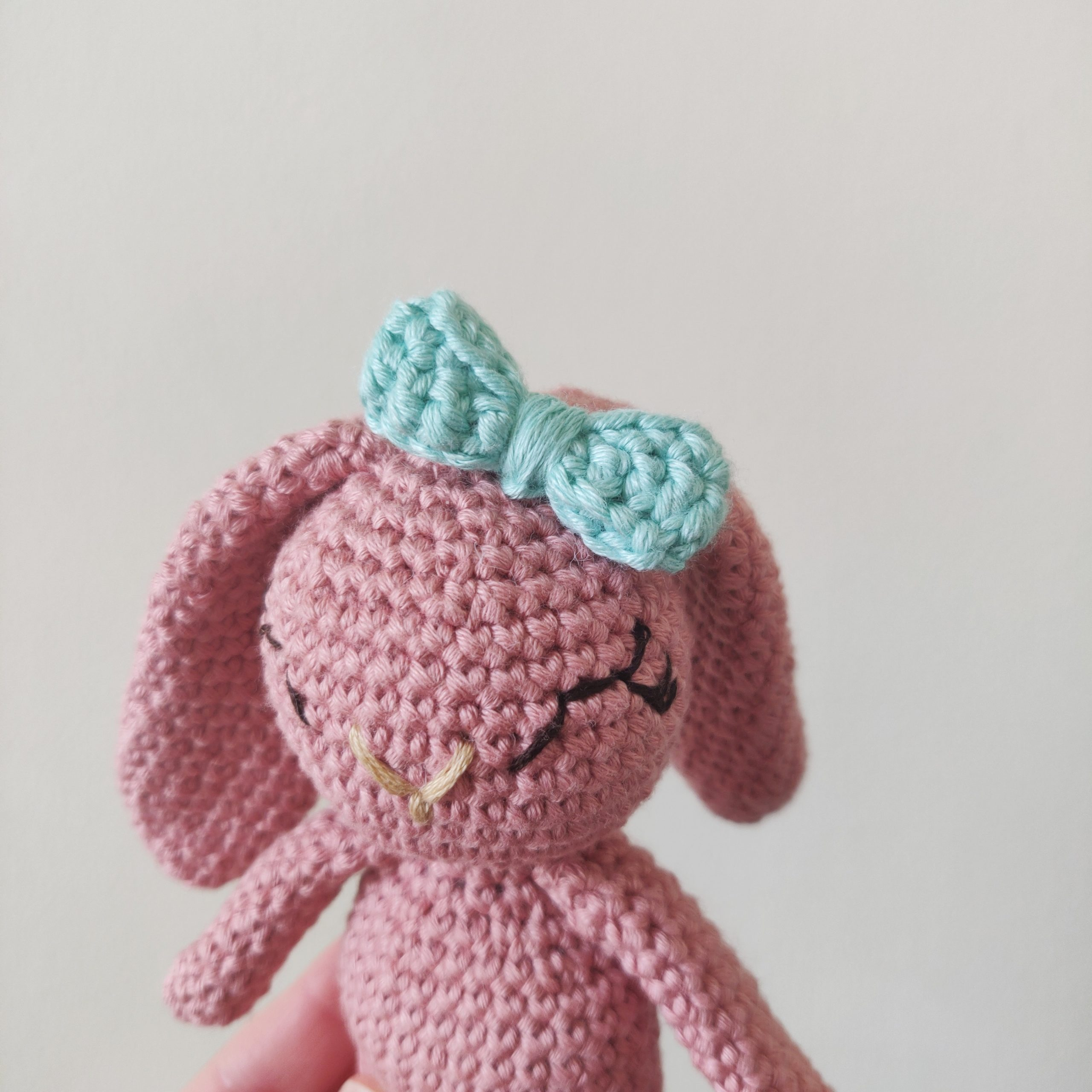 Pink crochet bunny with blue crochet bow.