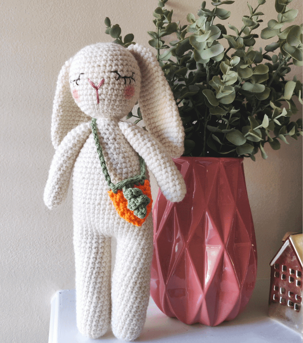 White crochet bunny with carrot purse on a mantle.