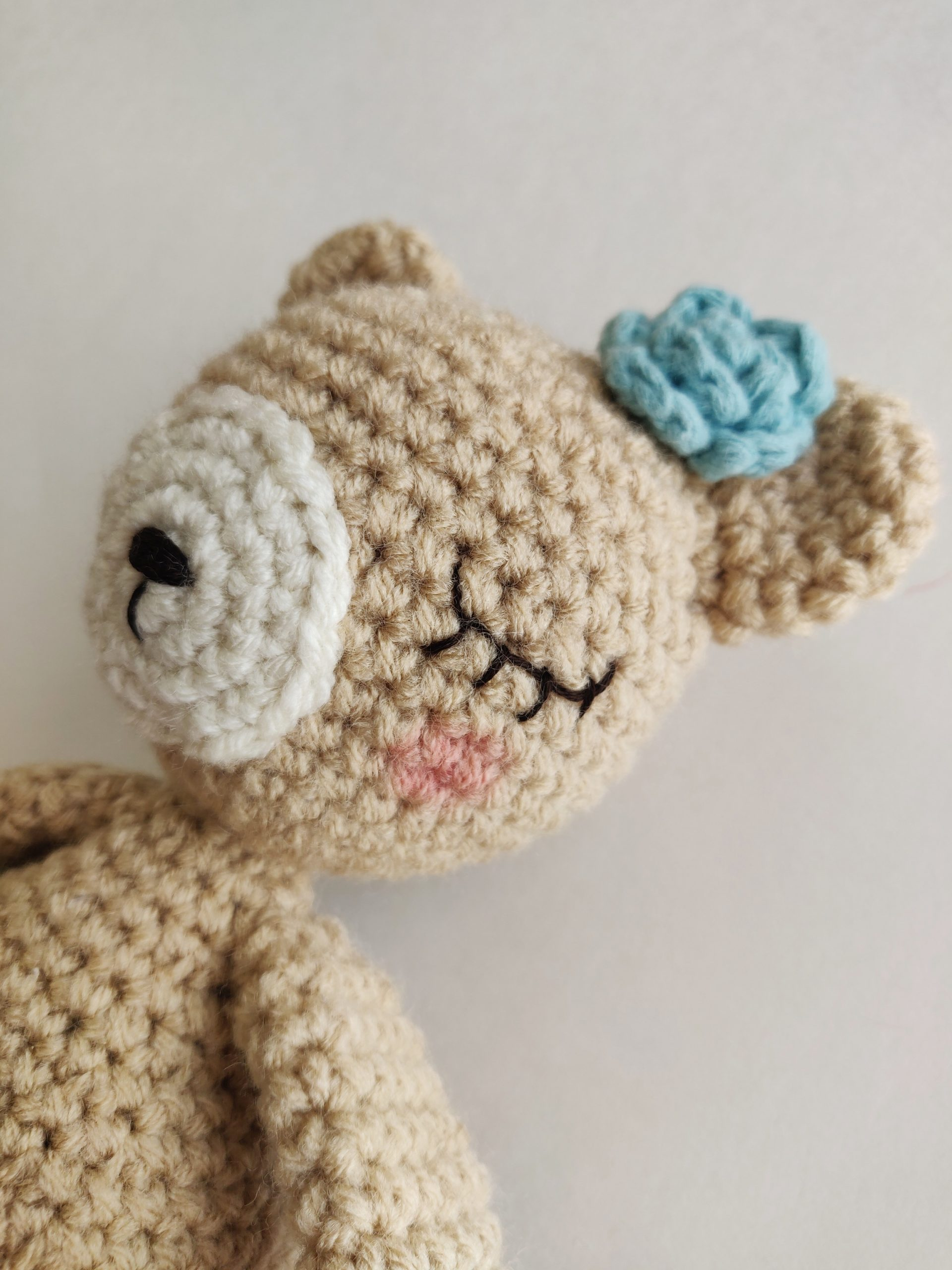 Sleepy eyed brown crochet bear and blue rose on ear.