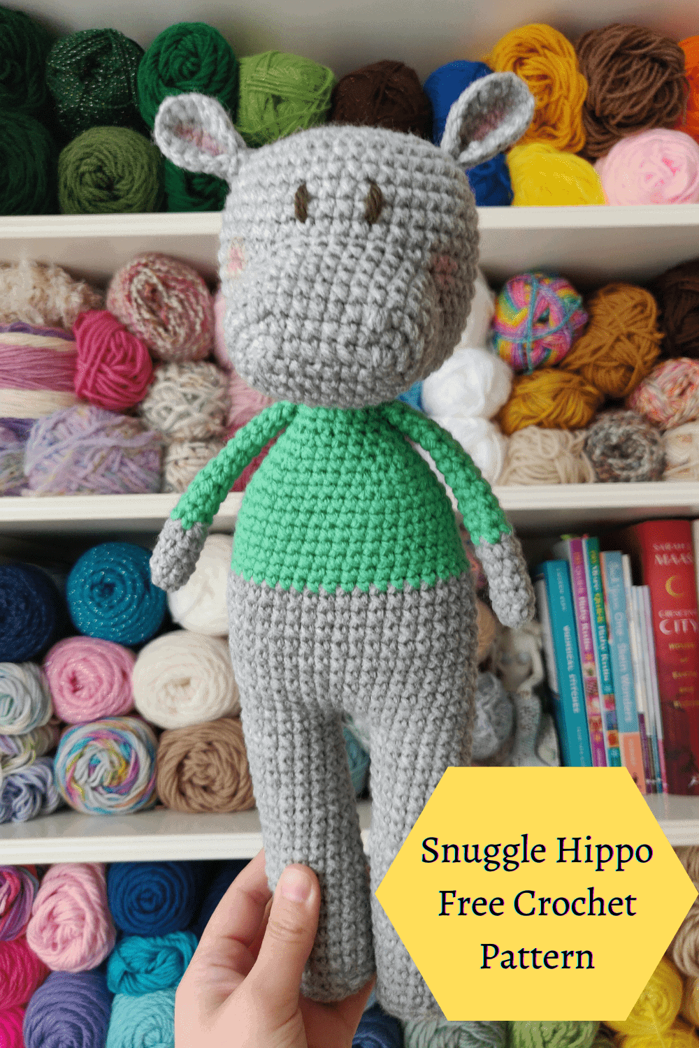 Gray crochet hippo with a green long sleeve shirt. Yarn in the background.
