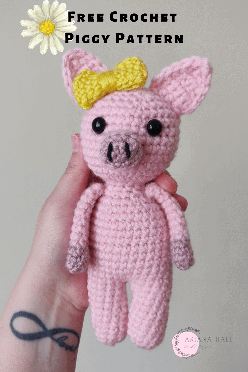 Pink crochet pig with a yellow crochet bow.
