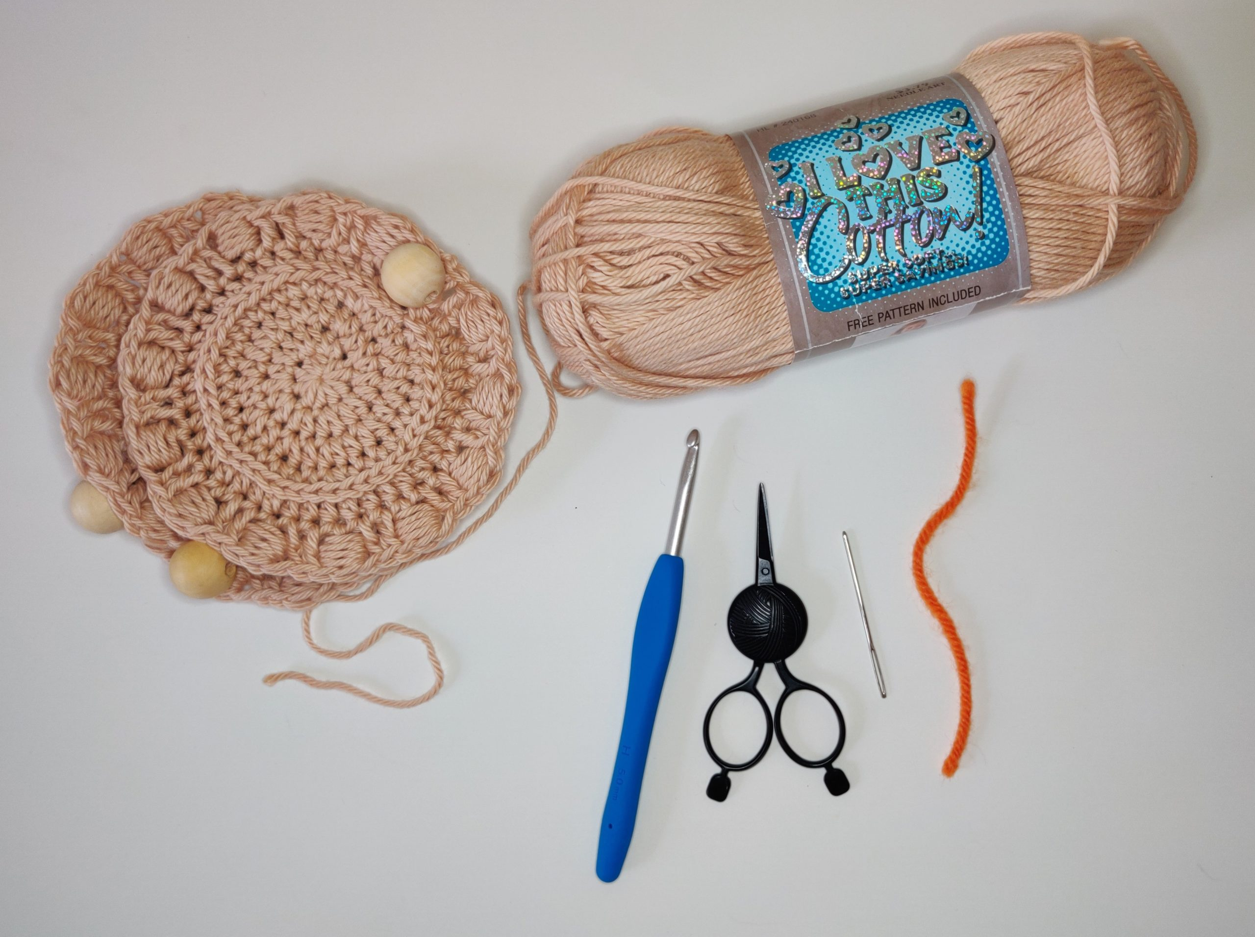 Materials for crochet, scissors, yarn and crochet hook.