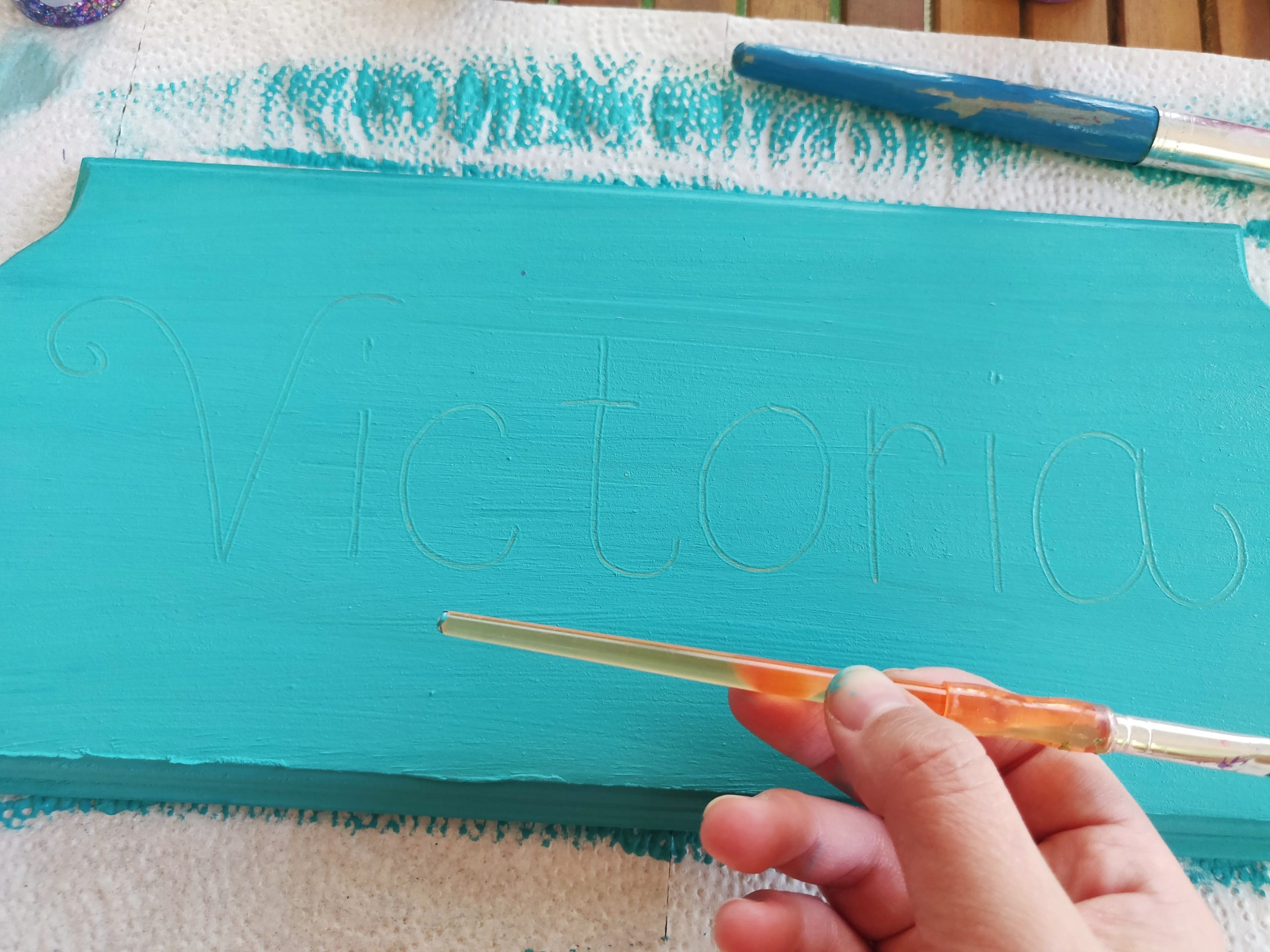 Writing the childs name with the end of a paintbrush