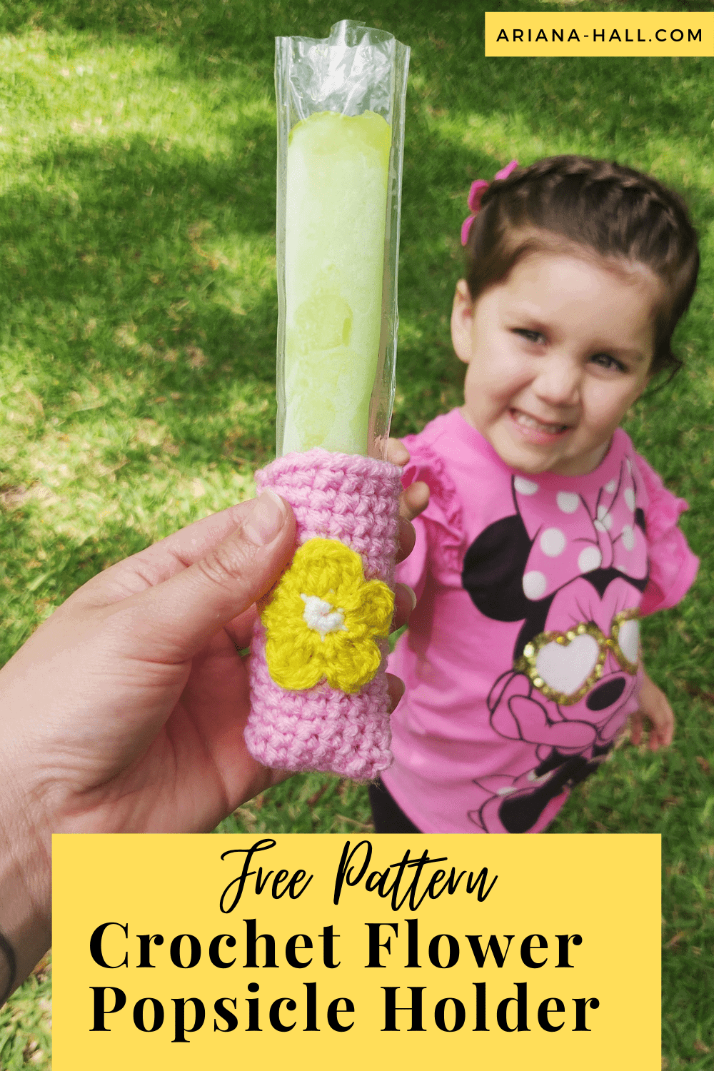 Pink crochet popsicle holder with flower in the middle.