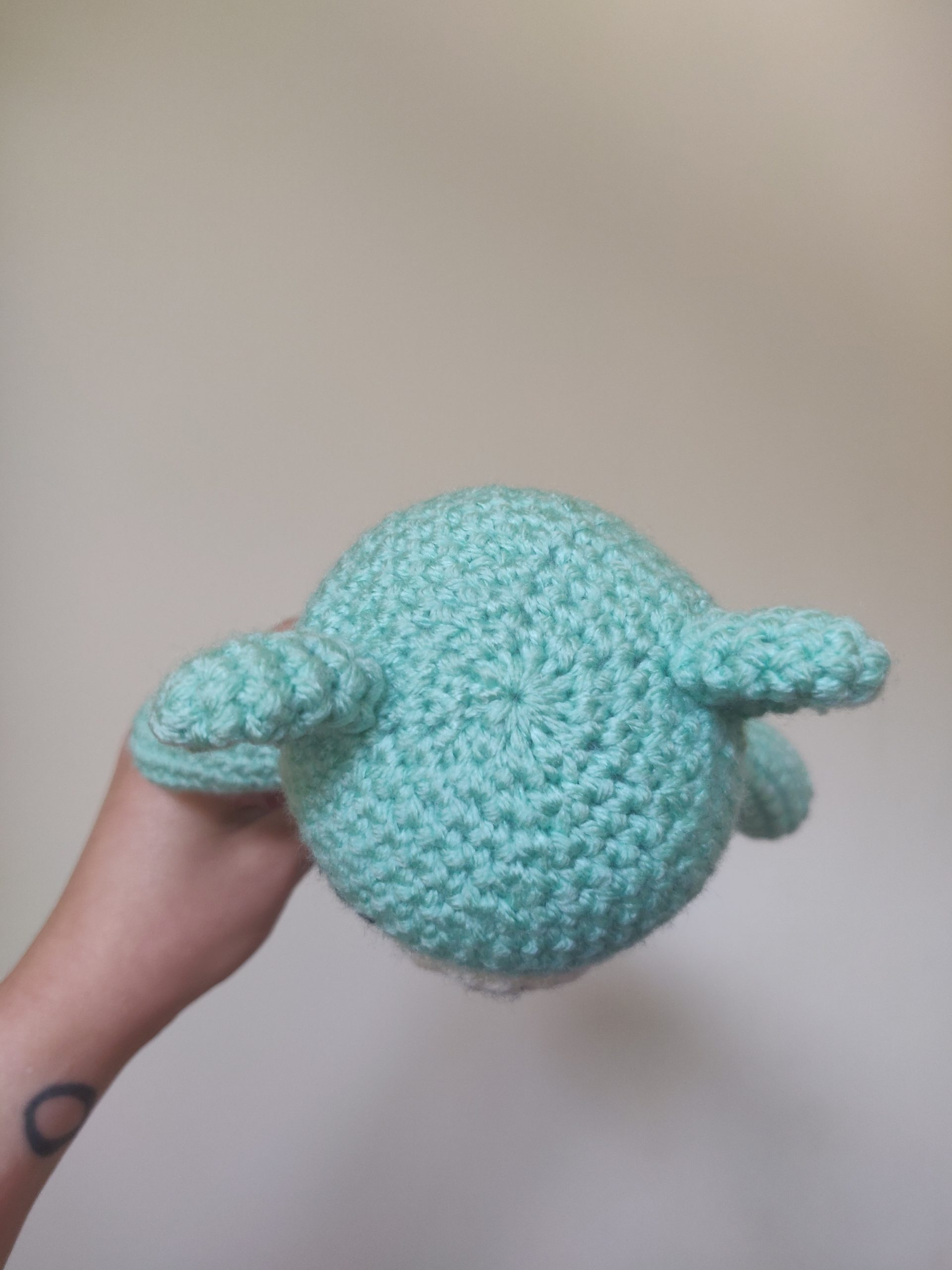 blue crochet bear with two ears sewn on.